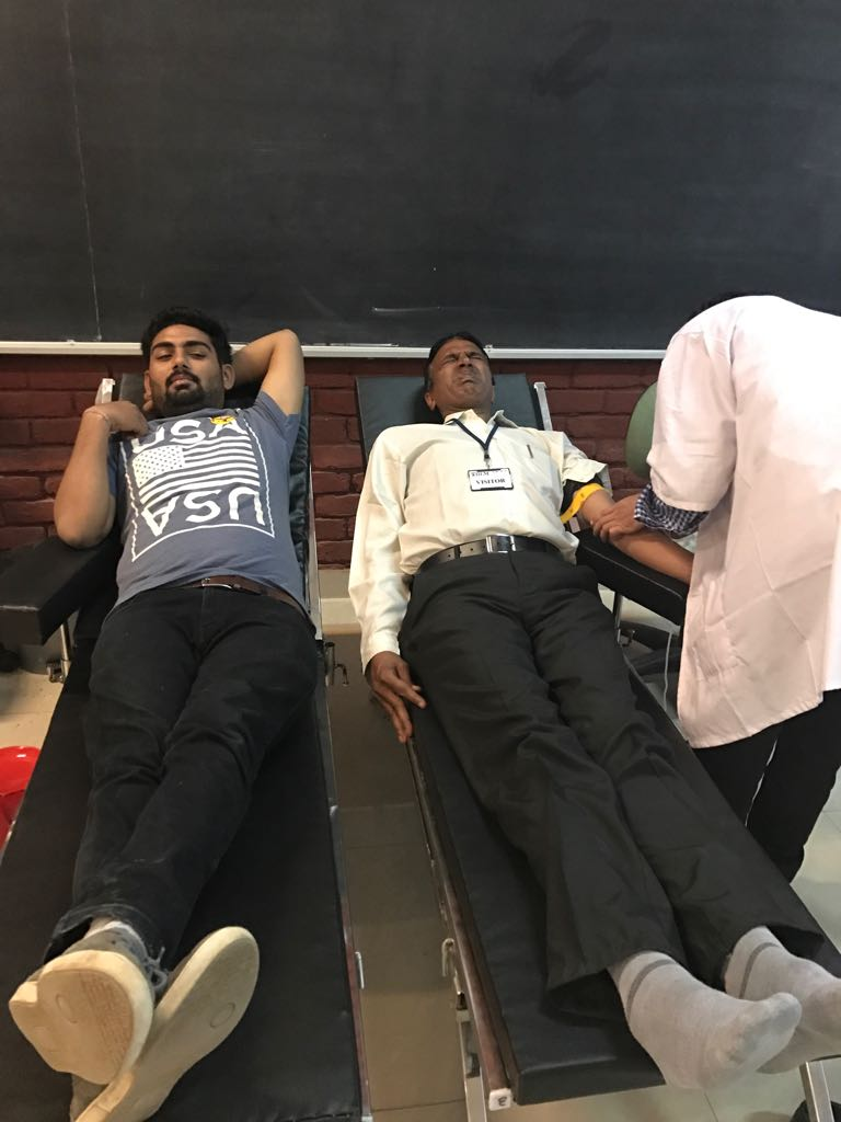 Student and Security Staff donating blood.